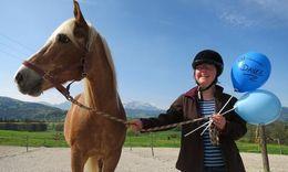 Sie sehen eine Frau die ein Pferd am Zügel hält