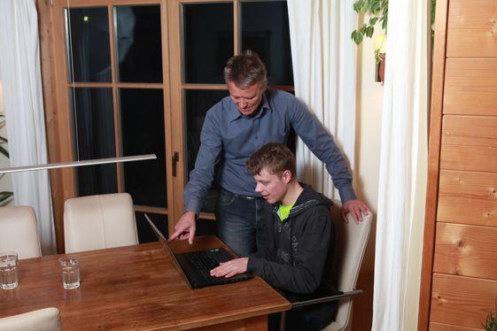 Einem Mann mit Behinderung wird der Umgang mit dem Computer erläutert