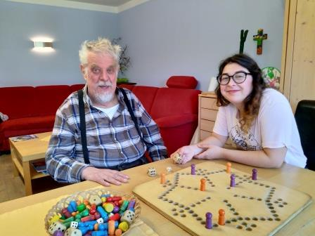 Sie sehen eine junge Frau und einen älteren Mann mit Behinderung bei einem Brettspiel