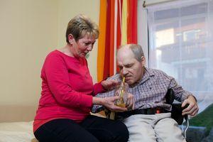 Eine Mitarbeiterin des Familien Entlastenden Dienstes unterstützt einen Gast beim Trinken