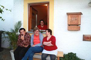 Einige Bewohner des Standortes Thundorf sitzen vor ihrem Wohnhaus