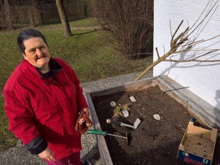 Sie sehen eine Frau mit Behinderung bei der Gartenarbeit